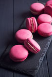 Bolinhos de amêndoa cor-de-rosa da framboesa no fundo preto Fotografia de Stock