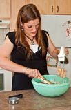 Bolinhos do cozimento da mulher nova com misturador Imagem de Stock Royalty Free