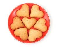 Bolinhos Heart-shaped no saucer vermelho fotos de stock