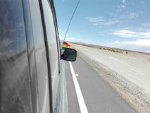Bolivia flag car ride desert. A car ride in Bolivia Royalty Free Stock Image