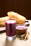 Bolivian Api with Pastel. Traditional Bolivian Api, a purple corn beverage, with pastel (deep-fried pastry filled with cheese) in the back, photographed with Stock Image