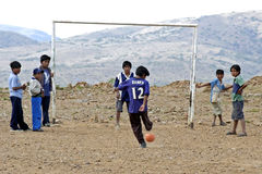 Bolivian boys playing football on a pebble field  Royalty Free Stock Photo