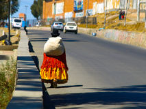 Bolivian cholita walking on the street of El Alto. Bolivian woman - cholita - with canvas sack, typical colorful clothes and hut walking on the street of El Alto Royalty Free Stock Photos