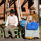 Bolivian family. A bolivian family of La Paz resting on a bench after going shopping for food, Bolivia Royalty Free Stock Photos