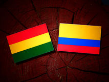 Bolivian flag with Colombian flag on a tree stump isolated Royalty Free Stock Photography