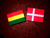 Bolivian flag with Danish flag on a tree stump isolated Royalty Free Stock Images