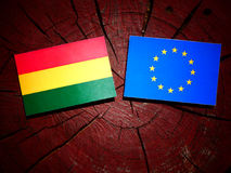 Bolivian flag with EU flag on a tree stump isolated. Bolivian flag with EU flag on a tree stump Stock Photography