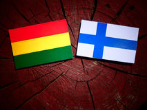 Bolivian flag with Finnish flag on a tree stump isolated Stock Image