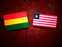 Bolivian flag with Liberian flag on a tree stump isolated Royalty Free Stock Photography
