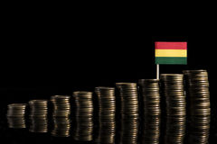 Bolivian flag with lot of coins isolated on black. Background Stock Photo