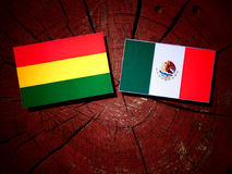Bolivian flag with Mexican flag on a tree stump isolated Royalty Free Stock Photos