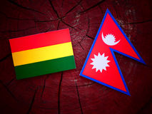 Bolivian flag with Nepali flag on a tree stump isolated Stock Photos