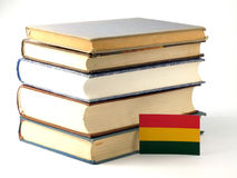 Bolivian flag with pile of books  on white background Royalty Free Stock Photo