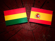 Bolivian flag with Spanish flag on a tree stump  Royalty Free Stock Photos