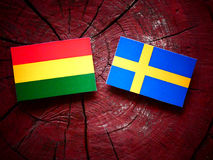 Bolivian flag with Swedish flag on a tree stump  Royalty Free Stock Images