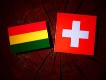 Bolivian flag with Swiss flag on a tree stump isolated Royalty Free Stock Photography