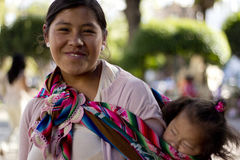 Bolivian mom. SUCRE, BOLIVIA - JANUARY 17, 2012: A bolivian mom carries her child on her back, tied up with a colorful traditional piece of fabric. January 17 Stock Photography