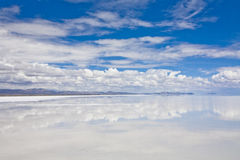 The Bolivian Salt Desert. Panorama of the salt desert of Uyuni, Bolivia, with its water reflecting the sky Royalty Free Stock Photos