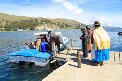Bolivian woman in traditional dress use ferry to cross titicaca Stock Images