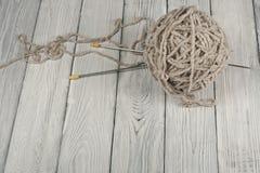 Boll av ull med eker för handgjort handarbete på trätabellen Handarbeteull och stickor Arkivbild