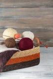 Boll av ull, visare och den woolen tröjan med eker för handgjort handarbete i korg på trätabellen Arkivbilder