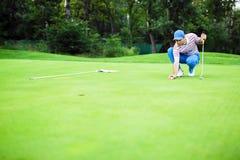 Boll för markering för golfspelare på den sättande gräsplanen Royaltyfri Bild