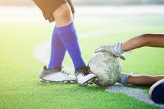 Boll för spark för fotbollspelare i hand av målvakten royaltyfri foto