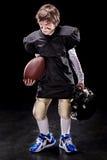 Boll och hjälm för rugby för ilsken fotbollsspelare för pojke amerikansk hållande Royaltyfria Foton