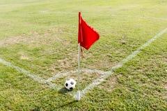 Boll och röd flagga i hörn av fotbollfältet Arkivbild