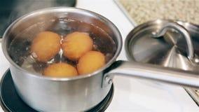 Bolla le uova del pollo in un vaso sulla stufa HD 1920 stock footage