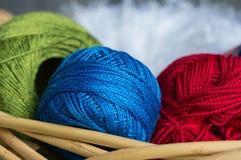 Bollar av blå och röd garn ett gräsplan, i en korg Fotografering för Bildbyråer