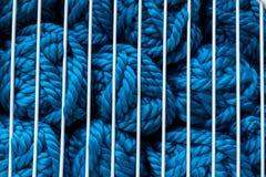 Bollar av blått handarbetegarn i raster för vit metall Arkivbilder