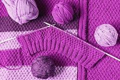Bollar av ull och oavslutat handarbete i violetsignaler, lekmanna- lägenhet royaltyfri fotografi