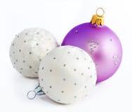 Bollar för lila och vit jul som isoleras på en vit Arkivbild