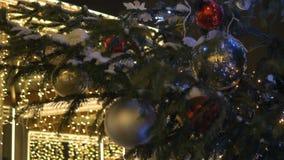 Bollar för ` s för nytt år hänger på julgranen, kulör belysning Guling klumpa ihop sig, gataträd som täckas med snö lager videofilmer