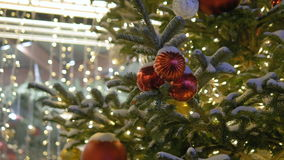 Bollar för ` s för nytt år hänger på julgranen, kulör belysning Röda bollar, gataträd som täckas med snö arkivfilmer