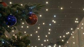 Bollar för ` s för nytt år hänger på julgranen, kulör belysning Röda bollar, gataträd som täckas med snö lager videofilmer