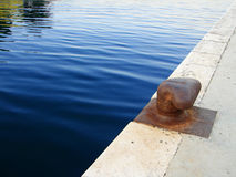 Bollard on dock. Rusted bollard on dock and calm blue sea Royalty Free Stock Images