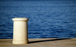 Bollard in early morning. Concrete mooring post/bollard in early morning with sea water in the background Royalty Free Stock Photography