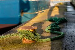 Bollard in the fishing port on the wharf. The wrapped rope moori. Ng fishing boats in the sea port. Autumn season Royalty Free Stock Photo