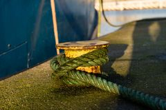 Bollard in the fishing port on the wharf. The wrapped rope moori. Ng fishing boats in the sea port. Autumn season Royalty Free Stock Photos