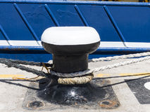 Bollard at a harbor pier with ship. Stock Images
