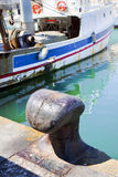 Bollard for mooring boats with fishing boat in the background Stock Photography