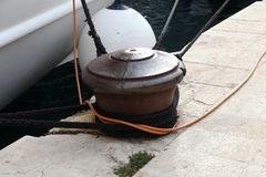Bollard with a mooring line wrapped around it.  royalty free stock photography