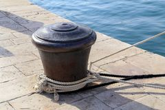 Bollard with a mooring line wrapped around it.  stock image