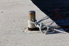 Bollard with a mooring line wrapped around it.  royalty free stock photos
