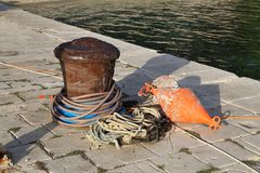 Bollard with a mooring line wrapped around it. Moored boats at the yacht harbor royalty free stock image