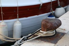 Bollard with a mooring line wrapped around it. Moored boats at the yacht harbor stock photo