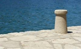 Bollard on the Pier. Mooring post on the pier by blue sea Stock Photos