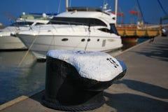 Bollard on the pier. Yacht on the background Stock Photos